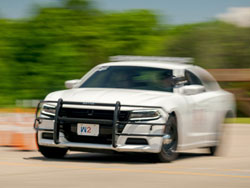 police car navigates through cone course