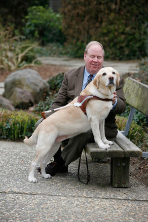 Michael Hingson and guide dog Roselle sit on a park bench.